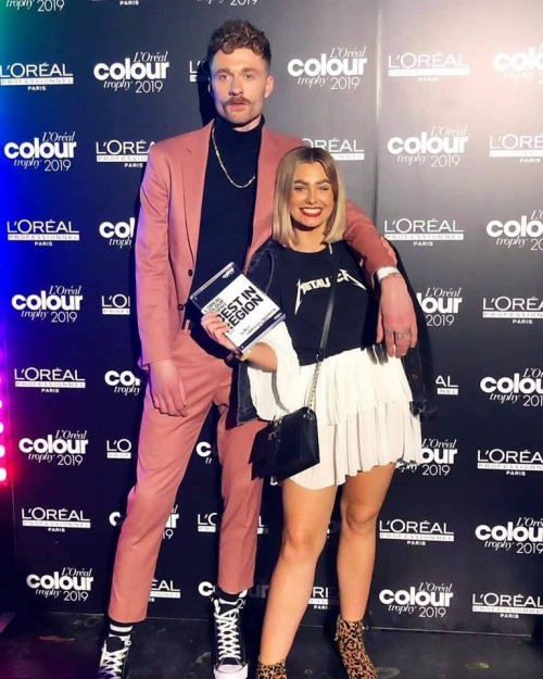Our senior stylist Ashley Wallce standing alongside her winning Men's Image style on her model at the L'Oreal Colour Trophy 2019.